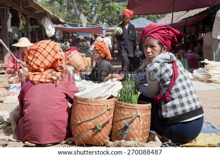 BURMA, SHAN STATE, SAMKAR -  FEBRUARY 25, 2011: Pa-O tribal woman in native costume are sitting on the market are selling home-made food. - stock photo