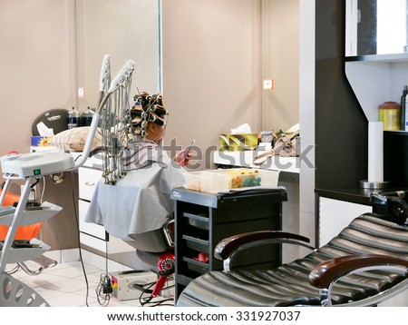 Burnaby, BC, Canada - October 16, 2015 : Woman having a perm and searching photo on cellphone in a hairdressing salon - stock photo