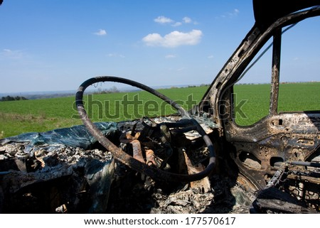 Burned car on the green grass with blue sky on the background - stock photo