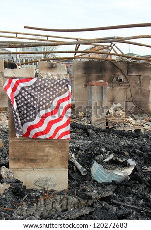Burned houses with flag - stock photo
