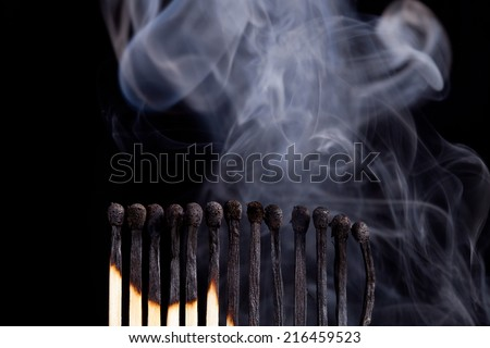 burned match sticks on dark background - stock photo