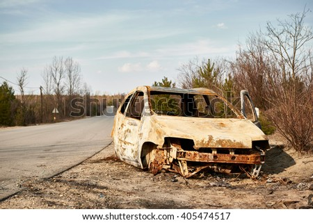 Burned to the ground car wreck on the side of the road  - stock photo