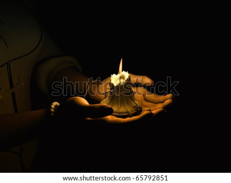 Burning a candle in his hand - stock photo