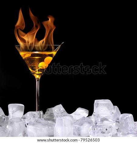 Burning alcoholic drink with ice cubes, isolated on black background - stock photo