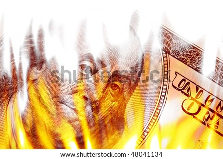 Burning American money with Benjamin Franklins face appearing on fire on a one hundred dollar bill. - stock photo