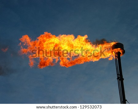 Burning and smoking oil flare - stock photo