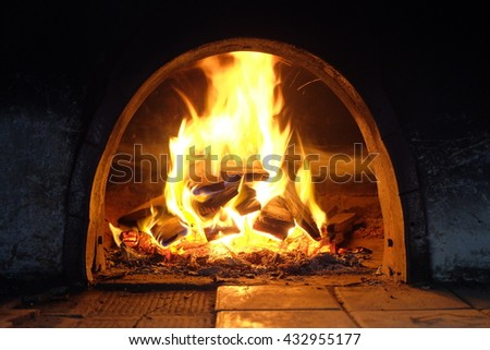 burning billets in fire-box of fireplace in country cottage - stock photo