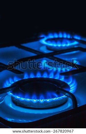 Burning blue gas. Focus on the front edge of the gas burners. black background from above can be used for your text - stock photo