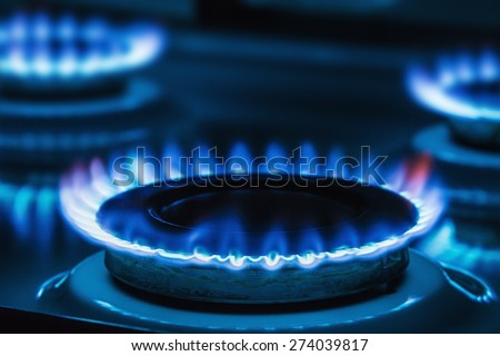 Burning blue gas on the stove. Focus on the front edge of the gas burners - stock photo