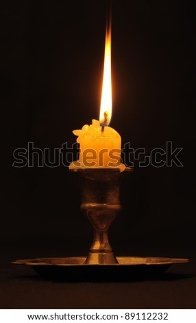 Burning candle. An ancient candlestick, a dark background - stock photo