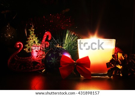 Burning candle, fir tree and Christmas decorations. - stock photo
