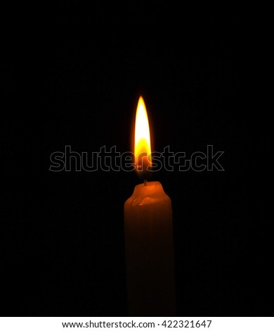 burning candle flame on the black background - stock photo
