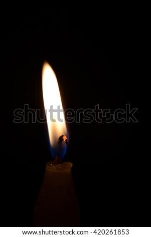 Burning candle isolated on black.  - stock photo