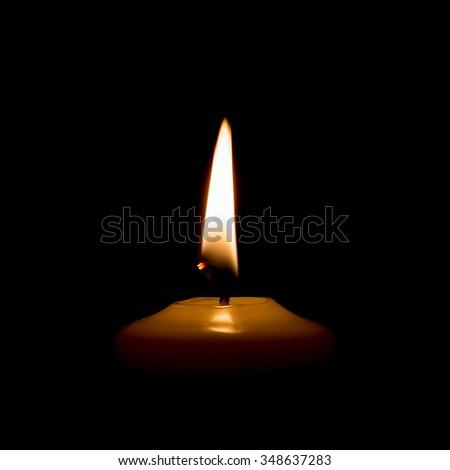 Burning candle isolated on black background. - stock photo