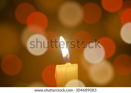 Burning candle light on abstract color bacground. Colorful bokeh - stock photo