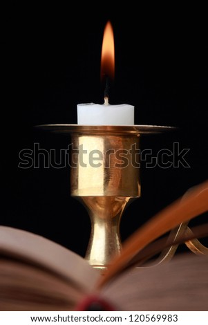 Burning candle on a black background - stock photo
