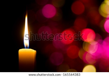 Burning candle on abstract color bacground - stock photo