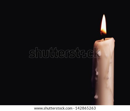 Burning candle over black. Is not isolated, just shot on black - stock photo