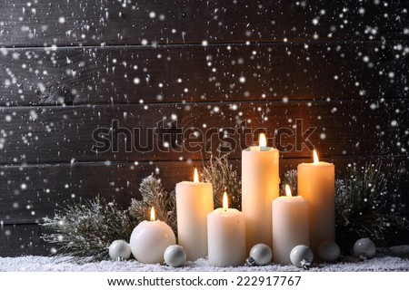 Burning candles and fir branch on snow - stock photo