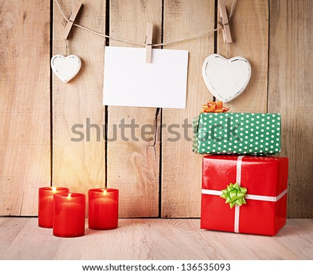 burning candles and gift boxes in front of a wooden wall with hearts and blank paper - stock photo