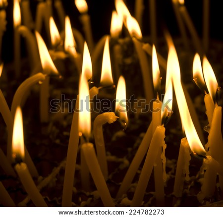 Burning candles in a church on a dark background - stock photo