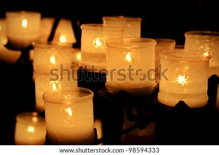 Burning candles in the dark church - stock photo