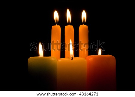 Burning candles over a black background - stock photo