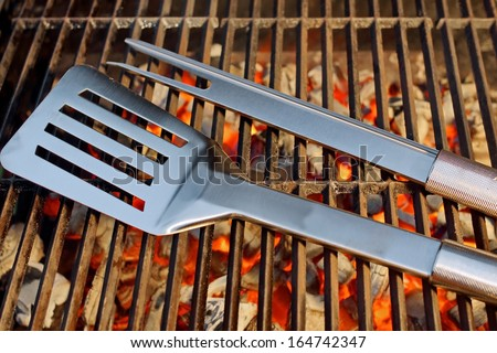 Burning charcoal in BBQ facilities and utensils on a hot grill - stock photo
