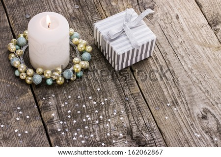 Burning Christmas candle and gift box on wooden background - stock photo