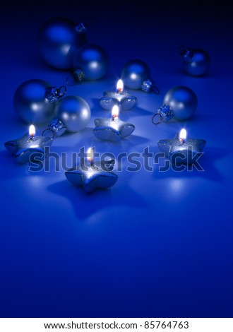 burning Christmas candles and ornaments on a blue background - stock photo