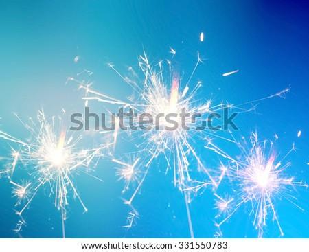 Burning christmas sparkler on blue background - stock photo