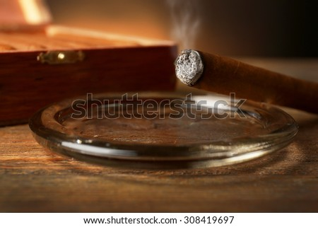 Burning cigar in ashtray on wooden table, closeup - stock photo