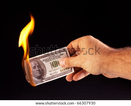 burning dollar in hand isolated on a black - stock photo