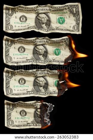Burning dollars on black background - stock photo