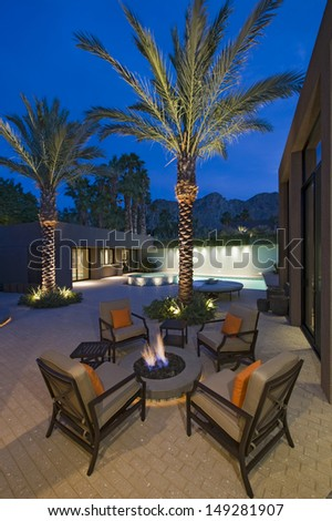 Burning fire pit surrounded by empty chairs on terrace of California home - stock photo