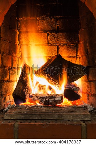 burning firewood in fire-box of fireplace in country cottage - stock photo