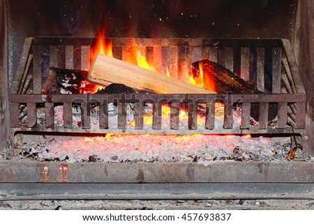 Burning firewood log on metal grate in a fireplace - stock photo