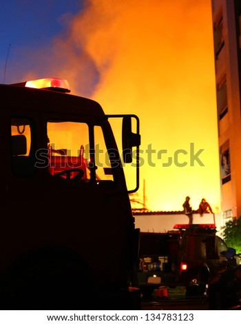 burning house, firefighters trying to extinguish the fire - stock photo