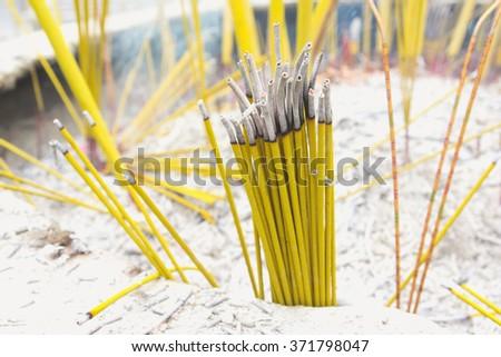 Burning incense sticks during prayer at Po Lin Monastery in Hong Kong. Hong Kong is popular tourist destination of Asia. - stock photo