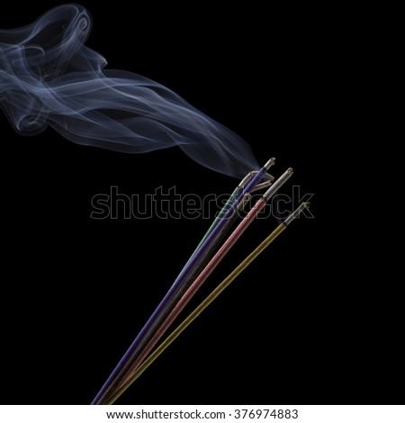 Burning incense sticks with smoke isolated on black - stock photo