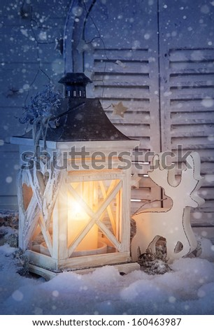 Burning lantern and christmas decoration in the evening - stock photo