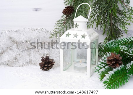 Burning lantern, spruce branches with cones and Christmas tinsel, horizontal - stock photo