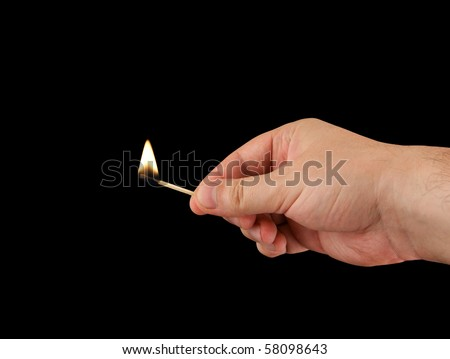 Burning match in hand on a black background - stock photo