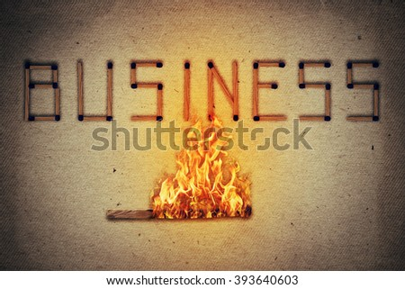 Burning match setting fire to its neighbors in arranged in shape of business word. Ignited match stick  as a symbol for business risks and dangers. - stock photo