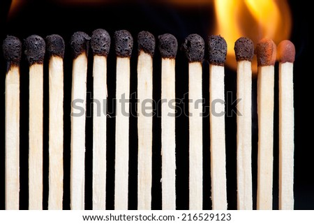 burning match sticks on dark background - stock photo