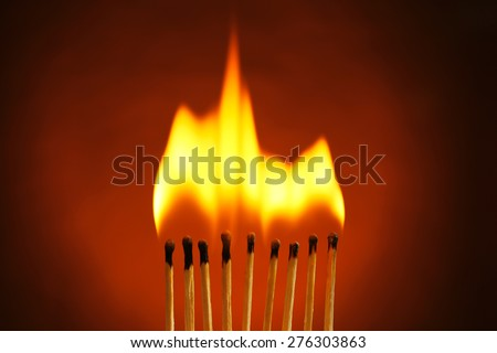 Burning matches on dark color background - stock photo