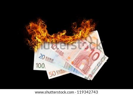 Burning money, euro bills on fire, isolated on black - stock photo