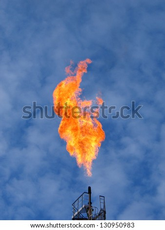 Burning oil flare over a blue sky - stock photo