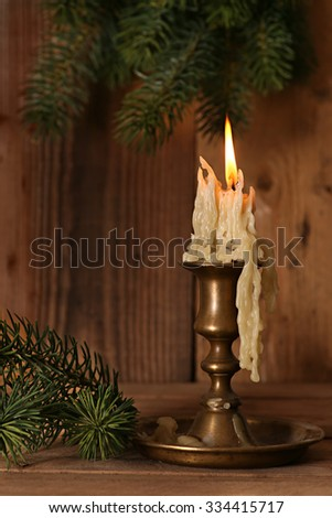 Burning old Candle Vintage Bronze candlestick on wooden background. Spruce branches. Christmas . - stock photo