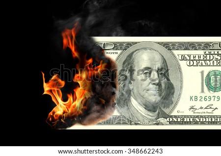 Burning one hundred dollar bill. Black background. - stock photo